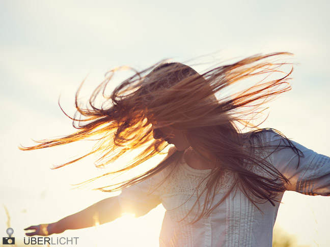 woman with backlight shaking head flying hair